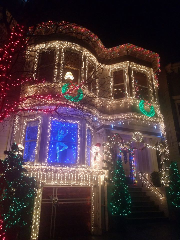 An Edwardian townhouse lit up with fairy lights. The shape and windows of the house are bordered in lights, two large wreaths are illuminated below the windows, the trees surrounding the house are also lit up in lights, a large ballerina is lit up with blue lights in the first floor window, and the garage door is wrapped with shiny red wrapping paper.