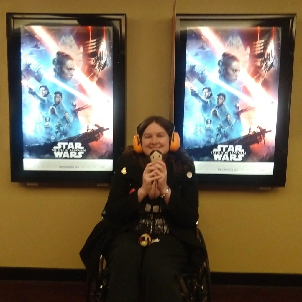 Photo of a white woman with brown hair wearing orange ear defenders and a black coat sitting in a wheelchair. She is holding a small Princess Leia plush. Behind her are two illuminated posters for Star Wars: The Rise of Skywalker.